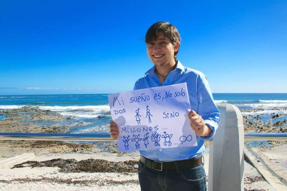 Michel Riquelme, activista transfeminista, no binario con una pancarta con dibujos que describen más géneros