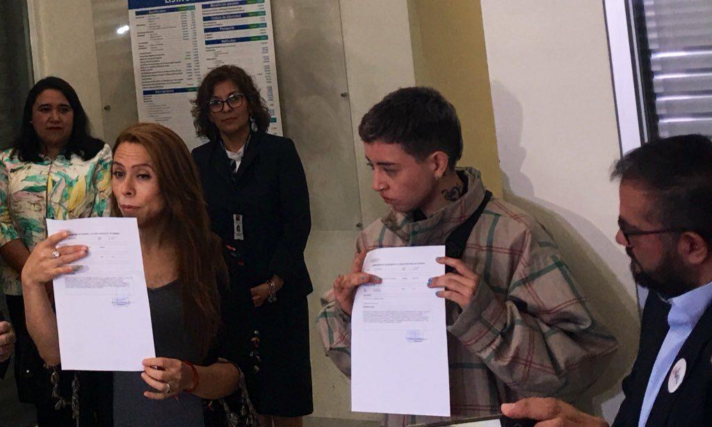 De izquierda a derecha Noah López y Valeria Pinto muestran la solicitud de hora para el cambio de nombre y sexo registral